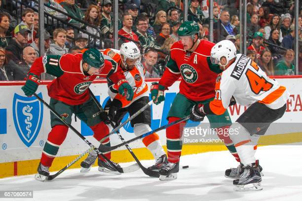 Zach Parise and Ryan Suter of the Minnesota Wild battle for the puck with PierreEdouard Bellemare and Andrew MacDonald of the Philadelphia Flyers...