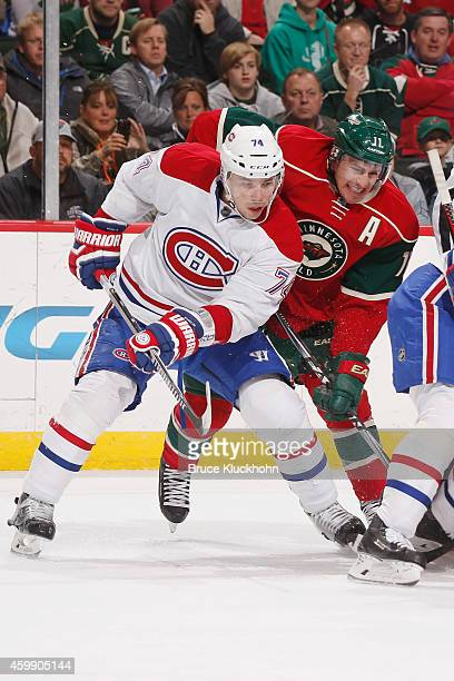 Zach Parise of the Minnesota Wild and Alexei Emelin of the Montreal Canadiens battle for position during a faceoff during the game on December 3 2014...