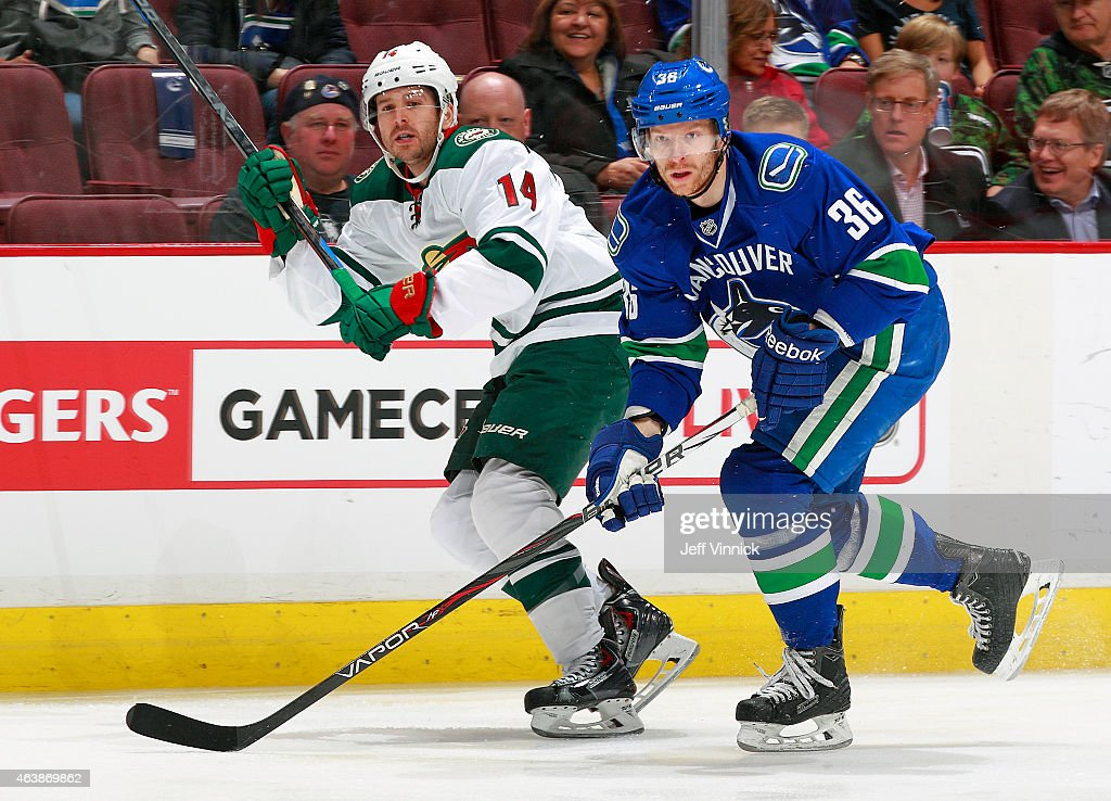 Zach Parise #11 of the Minnesota Wild and Dan Hamhuis #2 of the Vancouver Canucks skate up ice during their NHL game at Rogers Arena February 16, 2015 in Vancouver, British Columbia, Canada.