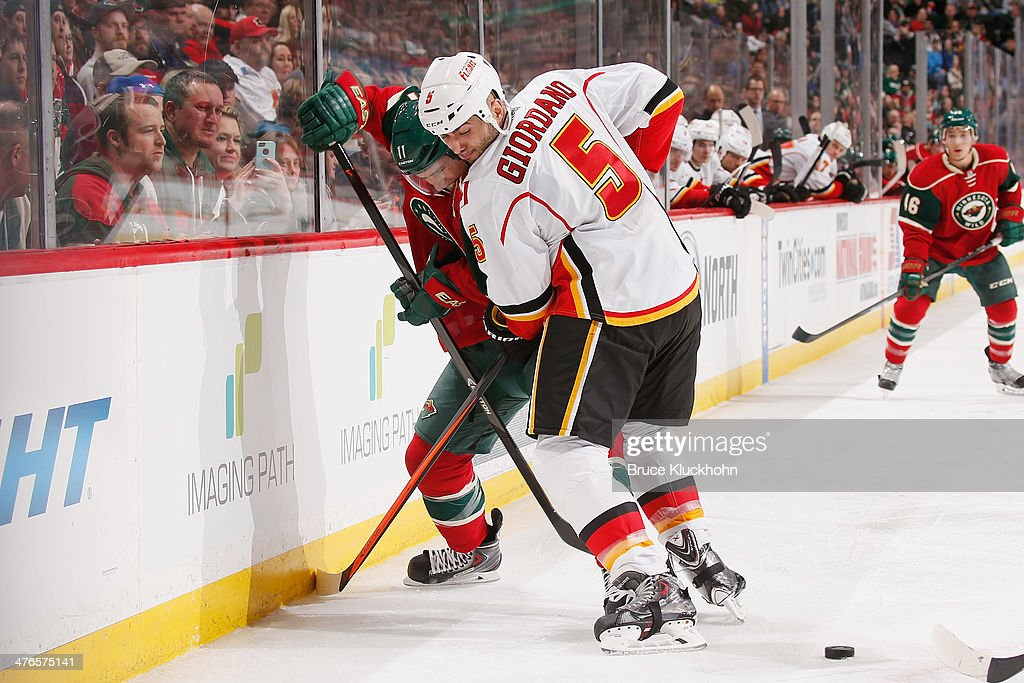 Zach Parise #11 of the Minnesota Wild and Mark Giordano #5 of the Calgary Flames battle for the puck along the boards during the game on March 3, 2014 at the Xcel Energy Center in St. Paul, Minnesota.