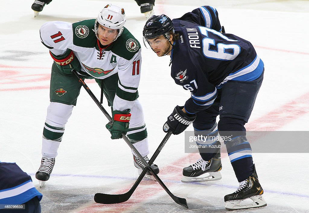 Zach Parise #11 of the Minnesota Wild and Michael Frolik #67 of the Winnipeg Jets get set for a second-period faceoff at the MTS Centre on April 7, 2014 in Winnipeg, Manitoba, Canada.