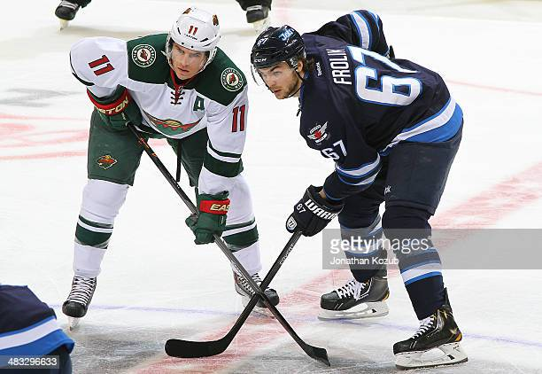 Zach Parise of the Minnesota Wild and Michael Frolik of the Winnipeg Jets get set for a secondperiod faceoff at the MTS Centre on April 7 2014 in...