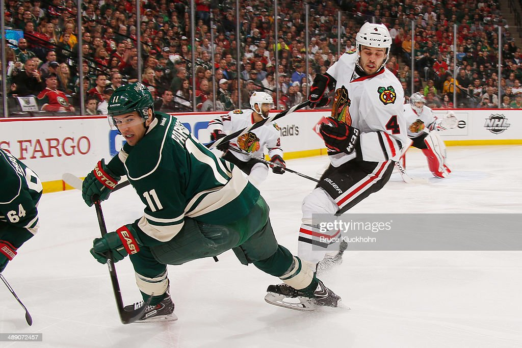Zach Parise #11 of the Minnesota Wild and Niklas Hjalmarsson #4 of the Chicago Blackhawks get tangled up during Game Four of the Second Round of the 2014 Stanley Cup Playoffs on May 9, 2014 at the Xcel Energy Center in St. Paul, Minnesota.
