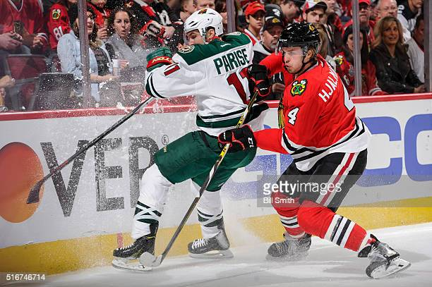 Zach Parise of the Minnesota Wild and Niklas Hjalmarsson of the Chicago Blackhawks get physical by the boards in the first period of the NHL game at...