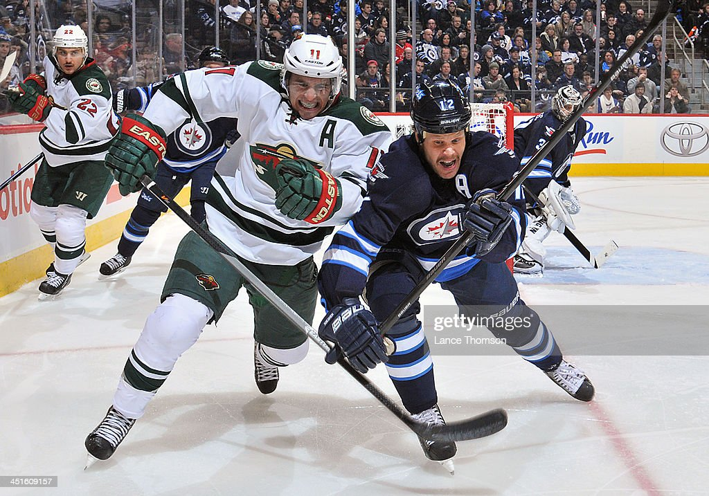 <a gi-track='captionPersonalityLinkClicked' href=/galleries/search?phrase=Zach+Parise&family=editorial&specificpeople=213606 ng-click='$event.stopPropagation()'>Zach Parise</a> #11 of the Minnesota Wild battles against <a gi-track='captionPersonalityLinkClicked' href=/galleries/search?phrase=Olli+Jokinen&family=editorial&specificpeople=202946 ng-click='$event.stopPropagation()'>Olli Jokinen</a> #12 of the Winnipeg Jets as they chase the loose puck during third period action at the MTS Centre on November 23, 2013 in Winnipeg, Manitoba, Canada.