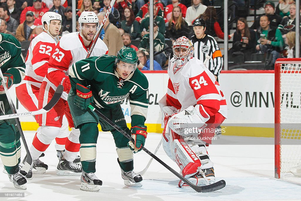 Zach Parise #11 of the Minnesota Wild gets position in front of the Detroit Red Wings goal while (L-R) Brian Lashoff #23 and goalie Petr Mrazek #34 of the Detroit Red Wings defend during the game on February 17, 2013 at the Xcel Energy Center in Saint Paul, Minnesota.