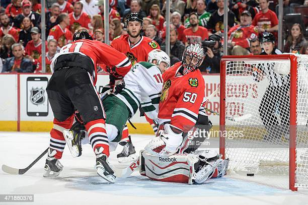 Zach Parise of the Minnesota Wild is tripped up after scoring on goalie Corey Crawford of the Chicago Blackhawks in the second period in Game One of...
