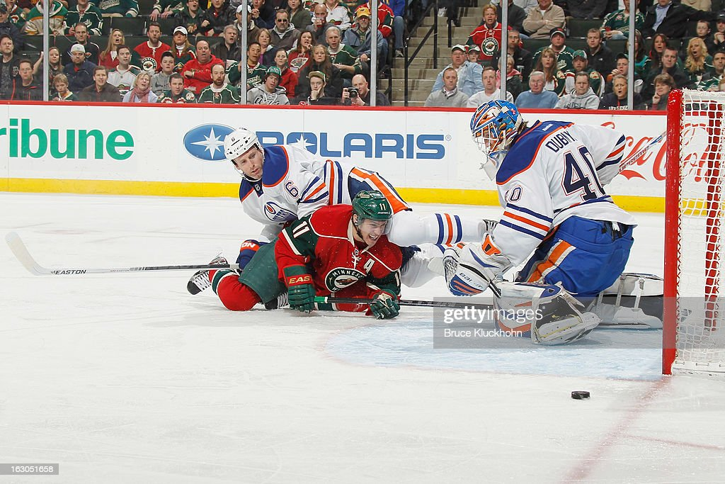 <a gi-track='captionPersonalityLinkClicked' href=/galleries/search?phrase=Zach+Parise&family=editorial&specificpeople=213606 ng-click='$event.stopPropagation()'>Zach Parise</a> #11 of the Minnesota Wild loses control of the puck on a scoring attempt with <a gi-track='captionPersonalityLinkClicked' href=/galleries/search?phrase=Ryan+Whitney&family=editorial&specificpeople=584338 ng-click='$event.stopPropagation()'>Ryan Whitney</a> #6 and goalie <a gi-track='captionPersonalityLinkClicked' href=/galleries/search?phrase=Devan+Dubnyk&family=editorial&specificpeople=2089794 ng-click='$event.stopPropagation()'>Devan Dubnyk</a> #40 of the Edmonton Oilers defending during the game on March 3, 2013 at the Xcel Energy Center in Saint Paul, Minnesota.