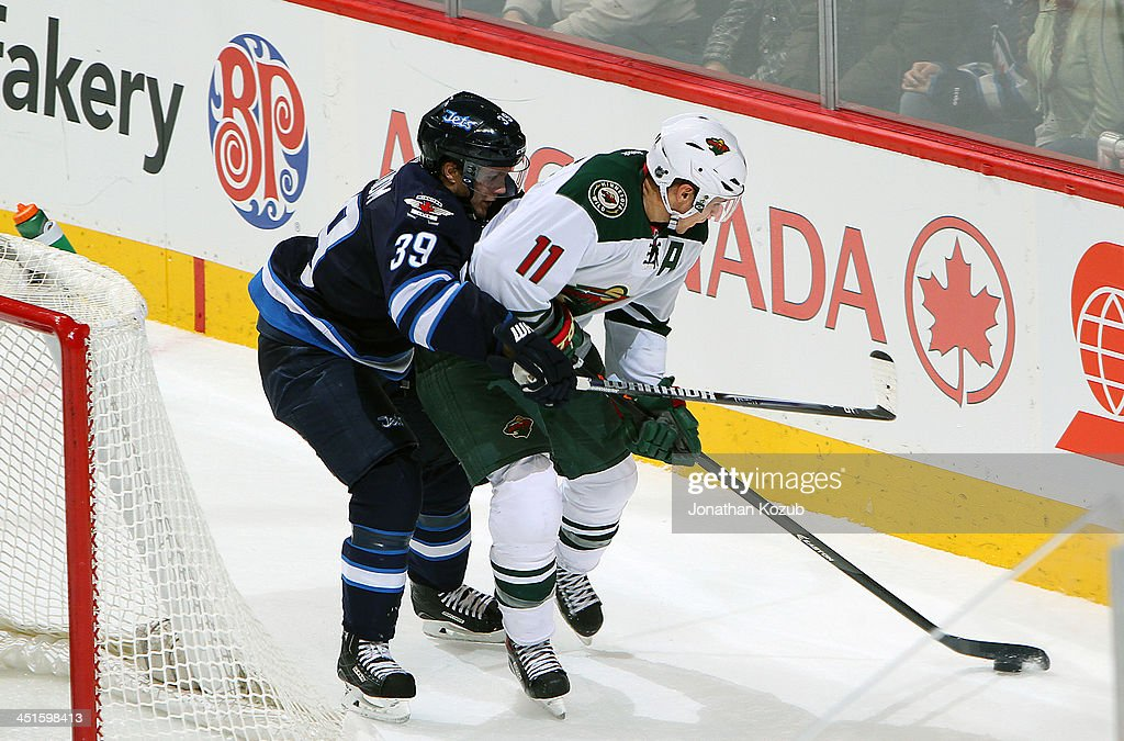 <a gi-track='captionPersonalityLinkClicked' href=/galleries/search?phrase=Zach+Parise&family=editorial&specificpeople=213606 ng-click='$event.stopPropagation()'>Zach Parise</a> #11 of the Minnesota Wild plays the puck behind the net as <a gi-track='captionPersonalityLinkClicked' href=/galleries/search?phrase=Tobias+Enstrom&family=editorial&specificpeople=2538468 ng-click='$event.stopPropagation()'>Tobias Enstrom</a> #39 of the Winnipeg Jets defends during second period action at the MTS Centre on November 23, 2013 in Winnipeg, Manitoba, Canada.