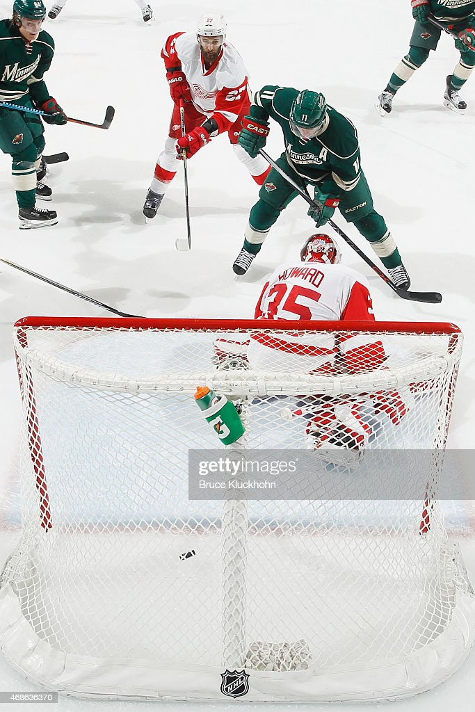 Zach Parise #11 of the Minnesota Wild scores a goal with Kyle Quincey #27 and goalie Jimmy Howard #35 of the Detroit Red Wings defending during the game on April 4, 2015 at the Xcel Energy Center in St. Paul, Minnesota.