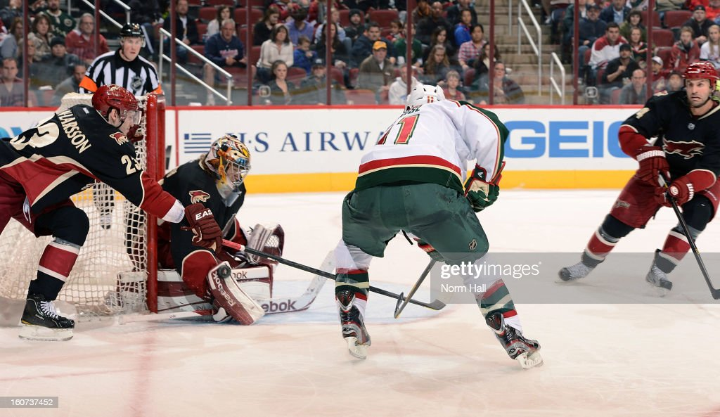 <a gi-track='captionPersonalityLinkClicked' href=/galleries/search?phrase=Zach+Parise&family=editorial&specificpeople=213606 ng-click='$event.stopPropagation()'>Zach Parise</a> #11 of the Minnesota Wild skates the puck in on goalie Mike Smith #41 of the Phoenix Coyotes as <a gi-track='captionPersonalityLinkClicked' href=/galleries/search?phrase=Oliver+Ekman-Larsson&family=editorial&specificpeople=5894618 ng-click='$event.stopPropagation()'>Oliver Ekman-Larsson</a> #23 tries to defend during the third period at Jobing.com Arena on February 4, 2013 in Glendale, Arizona.