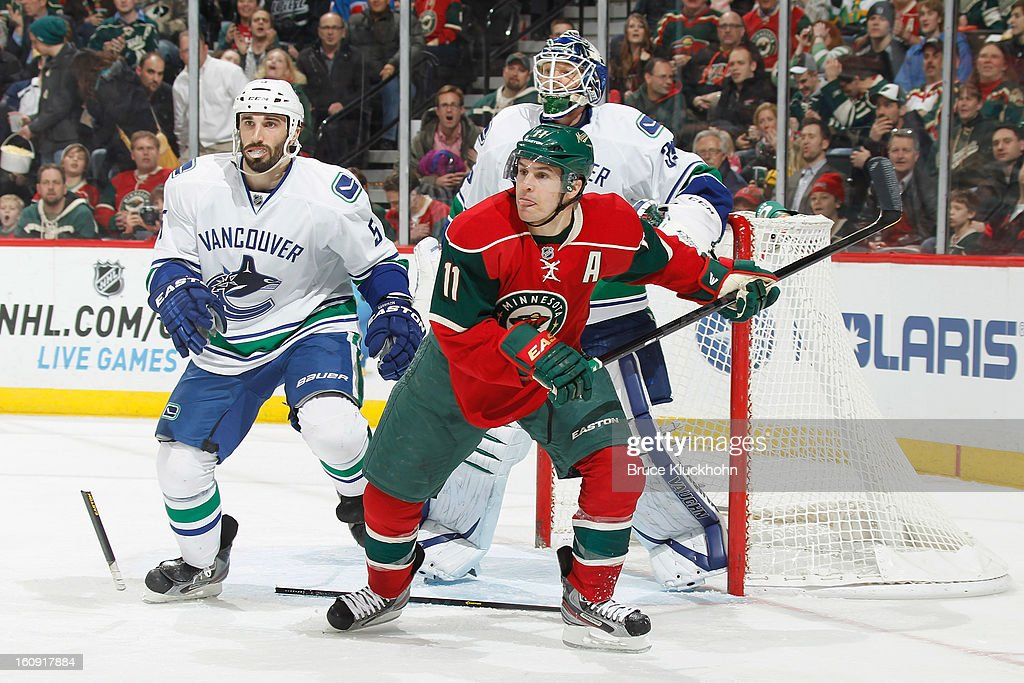 <a gi-track='captionPersonalityLinkClicked' href=/galleries/search?phrase=Zach+Parise&family=editorial&specificpeople=213606 ng-click='$event.stopPropagation()'>Zach Parise</a> #11 of the Minnesota Wild skates to the puck while <a gi-track='captionPersonalityLinkClicked' href=/galleries/search?phrase=Jason+Garrison&family=editorial&specificpeople=2143635 ng-click='$event.stopPropagation()'>Jason Garrison</a> #5 and goalie <a gi-track='captionPersonalityLinkClicked' href=/galleries/search?phrase=Cory+Schneider&family=editorial&specificpeople=696908 ng-click='$event.stopPropagation()'>Cory Schneider</a> #35 of the Vancouver Canucks defend during the game on February 7, 2013 at the Xcel Energy Center in Saint Paul, Minnesota.
