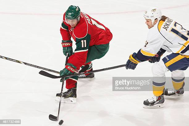 Zach Parise of the Minnesota Wild skates with the puck while Olli Jokinen of the Nashville Predators defends during the game on January 10 2015 at...