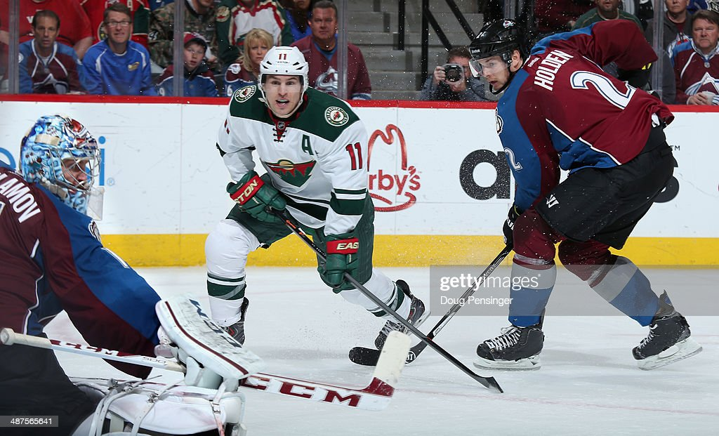 Zach Parise #11 of the Minnesota Wild takes a shot against goalie Semyon Varlamov #1 and Nick Holden #2 of the Colorado Avalanche in Game Seven of the First Round of the 2014 NHL Stanley Cup Playoffs at Pepsi Center on April 30, 2014 in Denver, Colorado. The Wild defeated the Avalanche in overtime 5-4 to win the series.