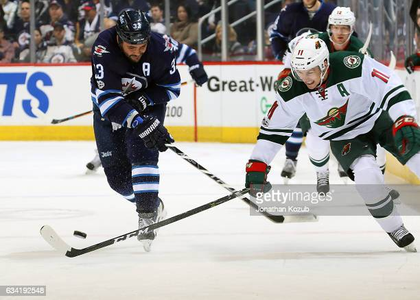 Zach Parise of the Minnesota Wild tries to deflect the puck past a defending Dustin Byfuglien of the Winnipeg Jets during first period action at the...