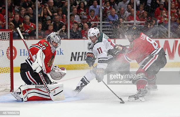 Zach Parise of the Minnesota Wild tries to get off a shot against Corey Crawford of the Chicago Blachawks as Nick Leddy defends in Game One of the...
