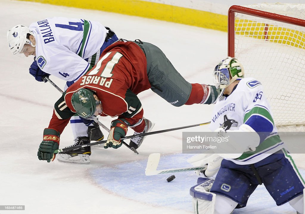 <a gi-track='captionPersonalityLinkClicked' href=/galleries/search?phrase=Zach+Parise&family=editorial&specificpeople=213606 ng-click='$event.stopPropagation()'>Zach Parise</a> #11 of the Minnesota Wild trips over the stick of <a gi-track='captionPersonalityLinkClicked' href=/galleries/search?phrase=Keith+Ballard+-+Ice+Hockey+Player&family=editorial&specificpeople=630546 ng-click='$event.stopPropagation()'>Keith Ballard</a> #4 of the Vancouver Canucks as <a gi-track='captionPersonalityLinkClicked' href=/galleries/search?phrase=Cory+Schneider&family=editorial&specificpeople=696908 ng-click='$event.stopPropagation()'>Cory Schneider</a> #35 deflects the puck during the third period of the game on March 10, 2013 at Xcel Energy Center in St Paul, Minnesota. The Wild defeated the Canucks 4-2.