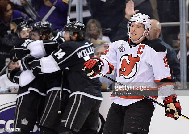 Zach Parise of the New Jersey Devils looks on as Dustin Brown Anze Kopitar Justin Williams of the Los Angeles Kings celebrate Kopitar's goal in the...