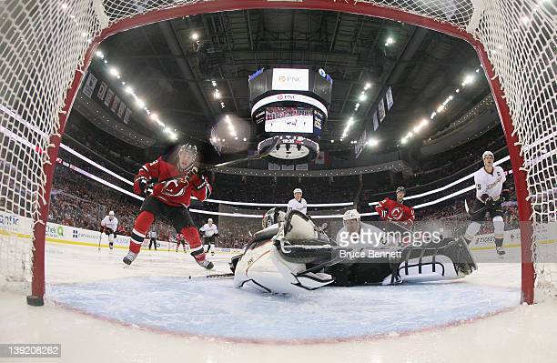 Zach Parise of the New Jersey Devils watches a shot by Adam Henrique elude goaltender Jonas Hiller of the Anaheim Ducks at 125 of the second period...