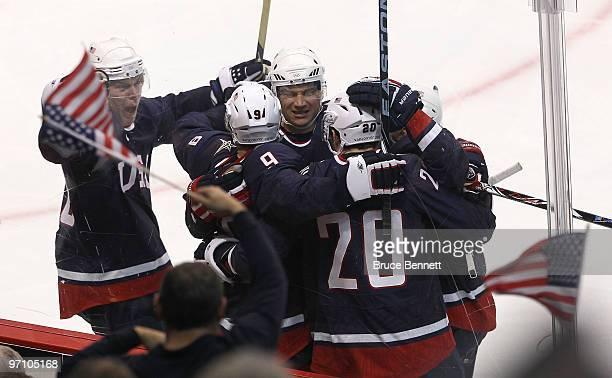 Zach Parise of the United States celebrates scoring past goalkeeper Miikka Kiprusoff of Finland during the ice hockey men's semifinal game between...