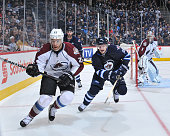 Zach Redmond of the Colorado Avalanche and Bryan Little of the Winnipeg Jets chase the puck towards the corner boards during overtime action on...