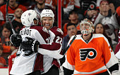 Zach Redmond of the Colorado Avalanche celebrates his third period goal against Steve Mason of the Philadelphia Flyers with teammate Maxime Talbot on...