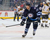 Zach Redmond of the Winnipeg Jets keeps an eye on the play during first period action against the Boston Bruins at the MTS Centre on April 10 2014 in...