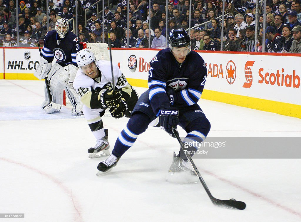 Zach Redmond #25 of the Winnipeg Jets plays the puck away from Joe Vitale #46 of the Pittsburgh Penguins as goaltender <a gi-track='captionPersonalityLinkClicked' href=/galleries/search?phrase=Ondrej+Pavelec&family=editorial&specificpeople=3644118 ng-click='$event.stopPropagation()'>Ondrej Pavelec</a> #31 keeps an eye on the play during second period action at the MTS Centre on February 15, 2013 in Winnipeg, Manitoba, Canada.