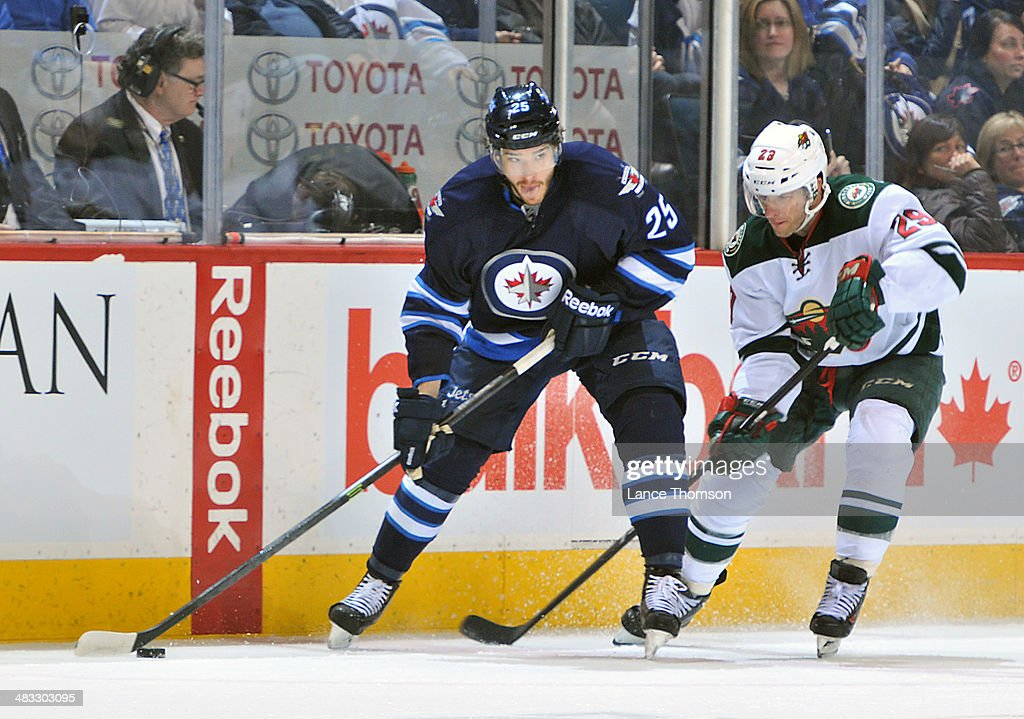 <a gi-track='captionPersonalityLinkClicked' href=/galleries/search?phrase=Zach+Redmond&family=editorial&specificpeople=8234699 ng-click='$event.stopPropagation()'>Zach Redmond</a> #25 of the Winnipeg Jets plays the puck down the ice as <a gi-track='captionPersonalityLinkClicked' href=/galleries/search?phrase=Jason+Pominville&family=editorial&specificpeople=570525 ng-click='$event.stopPropagation()'>Jason Pominville</a> #29 of the Minnesota Wild gives chase during third period action at the MTS Centre on April 7, 2014 in Winnipeg, Manitoba, Canada.