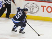 Zach Redmond of the Winnipeg Jets plays the puck up the ice during second period action against the Minnesota Wild at the MTS Centre on April 7 2014...