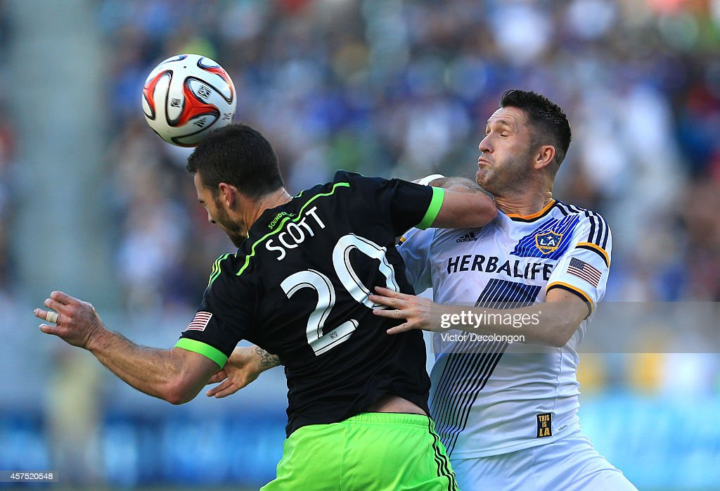 Zach Scott #20 of Seattle Sounders FC heads the ball from Robbie Keane #7 of Los Angeles Galaxy in the first half during the MLS match at StubHub Center on October 19, 2014 in Los Angeles, California.