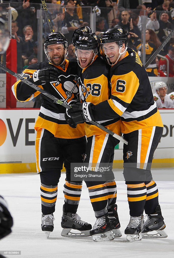 Zach Sill celebrates his first career NHL goal with Scott Harrington and Andrew Ebbett of the Pittsburgh Penguins during the second period against...