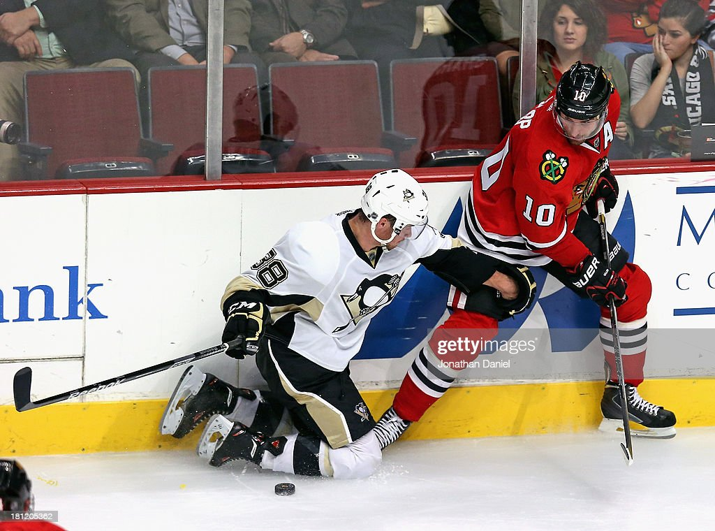 Zach Sill #38 of the Pittsburgh Penguins grabs the leg of Patrick Sharp #10 of the Chicago Blackhawks as they battle for the puck during an exhibition game at United Center on September 19, 2013 in Chicago, Illinois. The Penguins defeated the Blackhawks 4-3 in a shootout.