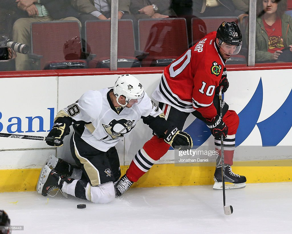 Zach Sill #38 of the Pittsburgh Penguins hits the ice as he battles for the puck with Patrick Sharp #10 of the Chicago Blackhawks during an exhibition game at United Center on September 19, 2013 in Chicago, Illinois. The Penguins defeated the Blackhawks 4-3 in a shootout.