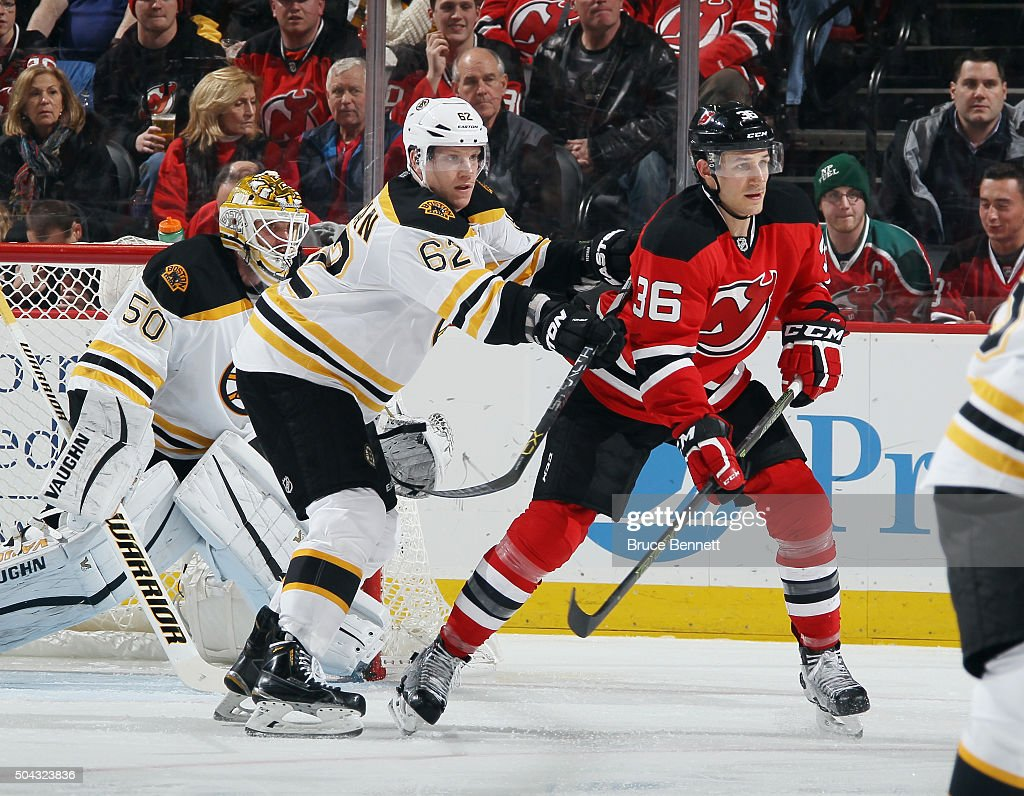 Zach Trotman of the Boston Bruins hits Jim O'Brien of the New Jersey Devils at the Prudential Center on January 8 2016 in Newark New Jersey The...