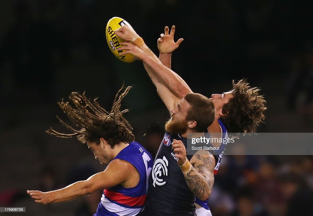 Zach Tuohy of the Blues and Luke Dahlhaus and Dylan Addison of the Bulldogs compete for the ball during the round 20 AFL match between the Carlton Blues and the Western Bulldogs at Etihad Stadium on August 10, 2013 in Melbourne, Australia.