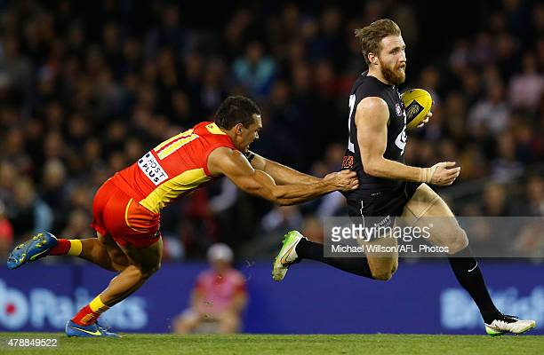 Zach Tuohy of the Blues is tackled by Harley Bennell of the Suns during the 2015 AFL round thirteen match between the Carlton Blues and the Gold...
