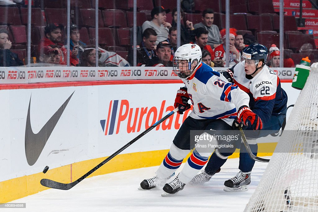 Zach Werenski #23 of Team United States chases the puck behind the net with Peter Cehlarik #22 of Team Slovakia following closely behind during the 2015 IIHF World Junior Hockey Championship game at the Bell Centre on December 29, 2014 in Montreal, Quebec, Canada.