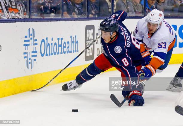 Zach Werenski of the Columbus Blue Jackets and Casey Cizikas of the New York Islanders battle for control of the puck during the first period on...