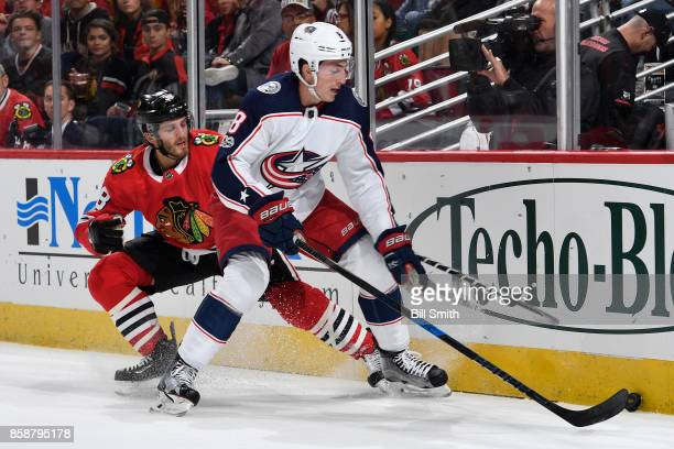 Zach Werenski of the Columbus Blue Jackets and Ryan Hartman of the Chicago Blackhawks battle for the puck in the first period at the United Center on...