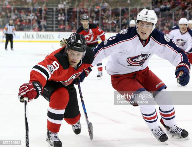 Zach Werenski of the Columbus Blue Jackets and Taylor Hall of the New Jersey Devils reach for the puck during the second period on March 19 2017 at...