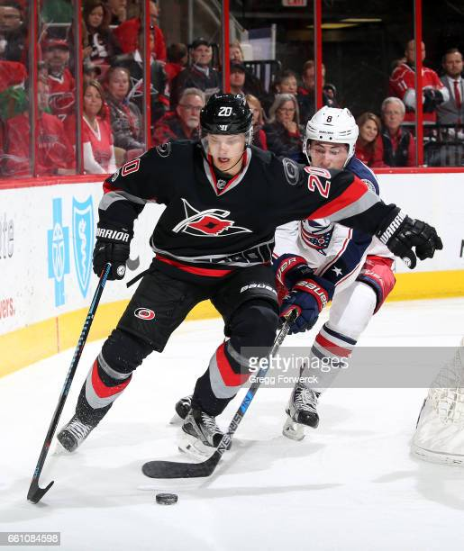 Zach Werenski of the Columbus Blue Jackets attempts to poke the puck away from Sebastian Aho of the Carolina Hurricanes during an NHL game on March...