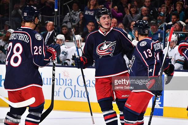 Zach Werenski of the Columbus Blue Jackets celebrate his first career NHL goal with teammates Oliver Bjorkstrand and Cam Atkinson of the Columbus...