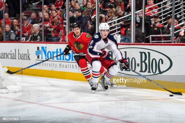 Zach Werenski of the Columbus Blue Jackets grabs the puck ahead of Richard Panik of the Chicago Blackhawks in the third period at the United Center...