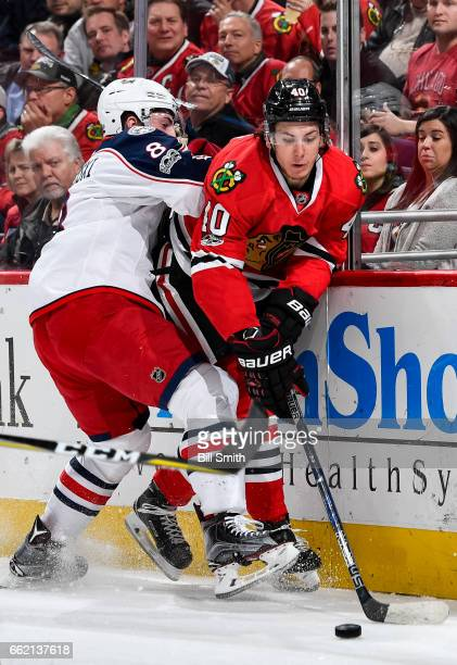 Zach Werenski of the Columbus Blue Jackets hits John Hayden of the Chicago Blackhawks in the first period at the United Center on March 31 2017 in...