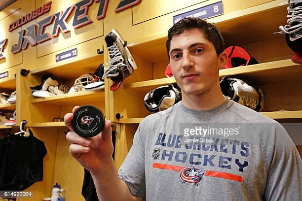 Zach Werenski of the Columbus Blue Jackets poses with the puck from his first career NHL goal during a game against the San Jose Sharks on October 15...