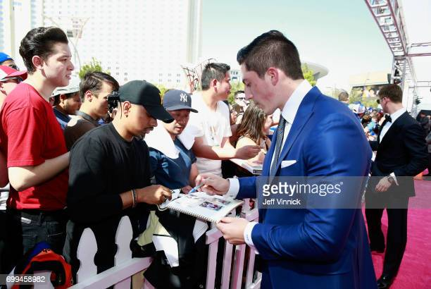 Zach Werenski of the Columbus Blue Jackets signs an autograph as he arrives on the magenta carpet for the 2017 NHL Awards at TMobile Arena on June 21...