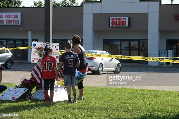 Zach Zoe and Melissa Cates add to a makeshift memorial near the scene of a shooting at a Armed Forces Career Center/National Guard recruitment office...