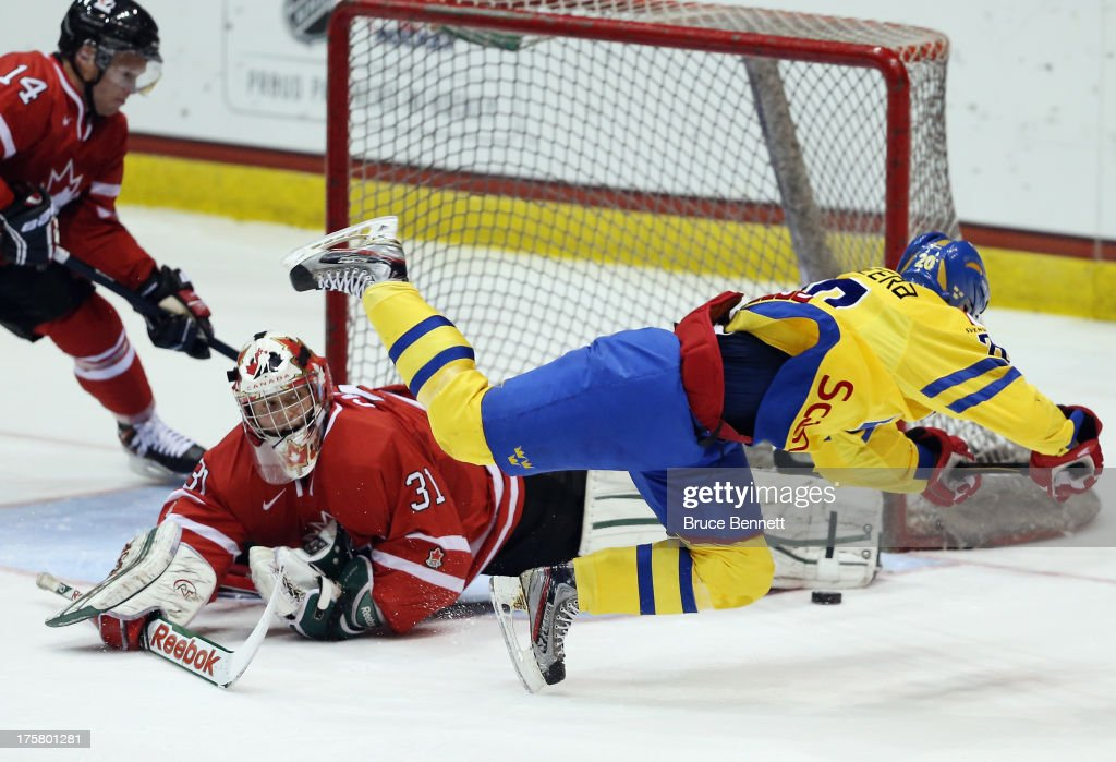 <a gi-track='captionPersonalityLinkClicked' href=/galleries/search?phrase=Zachary+Fucale&family=editorial&specificpeople=9959699 ng-click='$event.stopPropagation()'>Zachary Fucale</a> #31 of Team Canada makes the pad save on Gustav Possler #20 of Team Sweden during the 2013 USA Hockey Junior Evaluation Camp at the Lake Placid Olympic Center on August 8, 2013 in Lake Placid, New York.