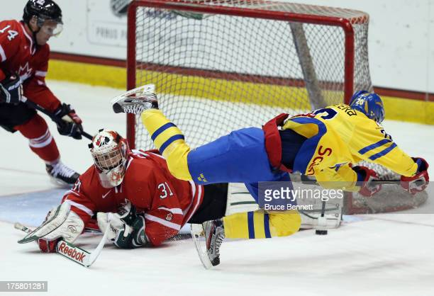 Zachary Fucale of Team Canada makes the pad save on Gustav Possler of Team Sweden during the 2013 USA Hockey Junior Evaluation Camp at the Lake...